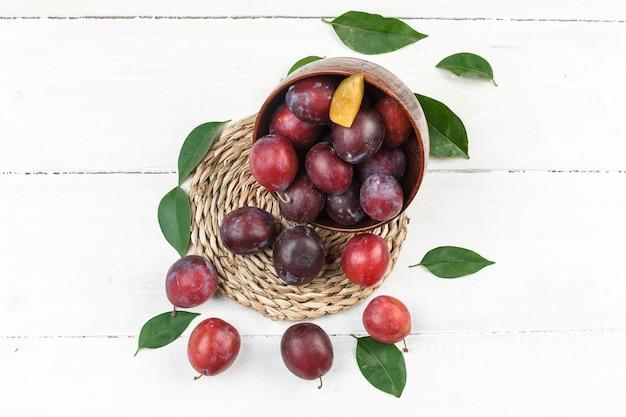 Vue grand angle un bol de prunes sur napperon en osier sur la surface de la planche de bois blanc. horizontal