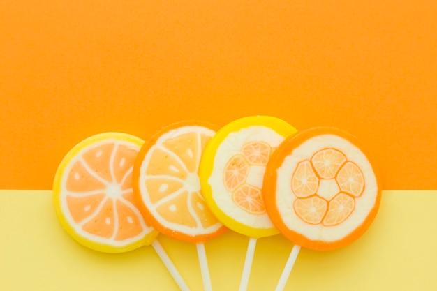 Vue grand angle de bonbons aux agrumes sur fond jaune et orange