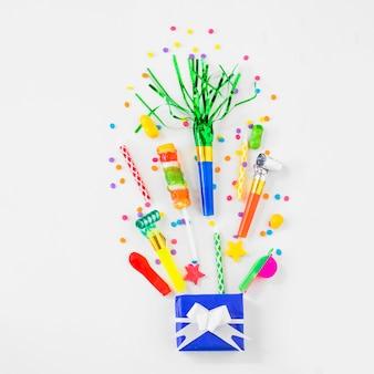 Vue grand angle de bonbons de cadeau d'anniversaire et accessoires de fête sur une surface blanche