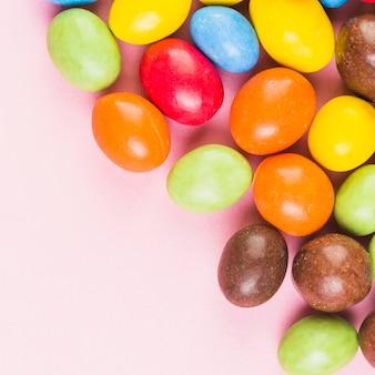 Vue grand angle de bonbons colorés sur une surface rose