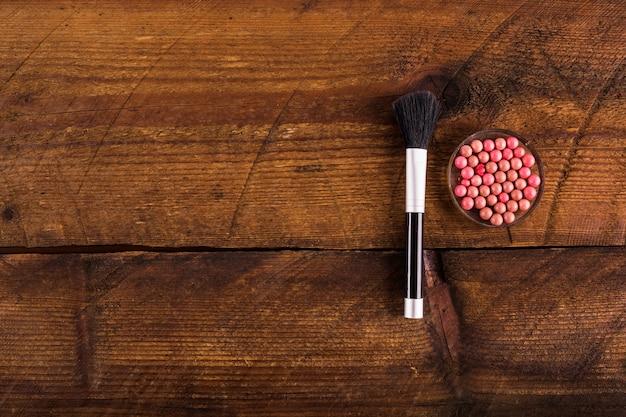 Vue grand angle de boules de poudre et pinceau de maquillage sur fond en bois