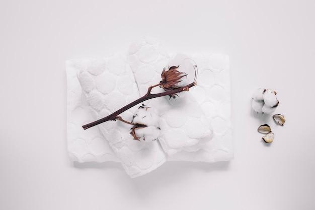 Vue grand angle de brindille de coton et de serviettes sur une surface blanche