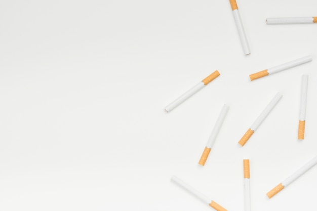Vue grand angle de cigarettes contre la surface blanche