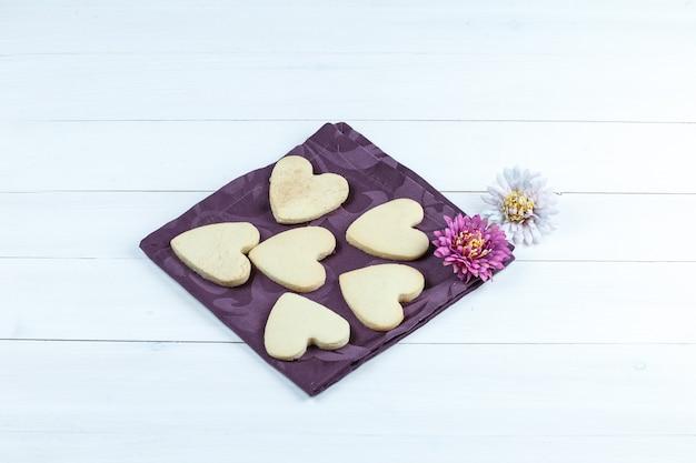 Vue grand angle de cookies en forme de coeur en napperon avec des fleurs sur fond de planche de bois blanc. horizontal