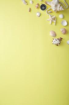 Vue grand angle de coquillages par des jumelles et des bijoux sur jaune