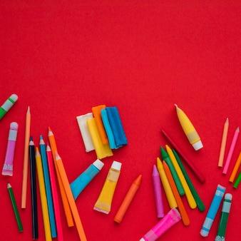 Vue grand angle de couleurs de peinture vives sur fond rouge