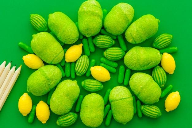 Vue grand angle, de, crayons, et, divers bonbons sucrés, sur, toile verte, toile de fond