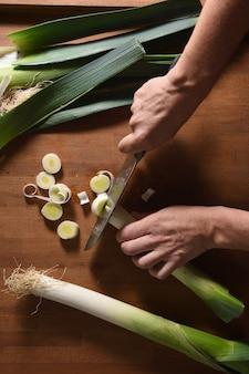 Vue grand angle d'un cuisinier coupant un poireau sur bois
