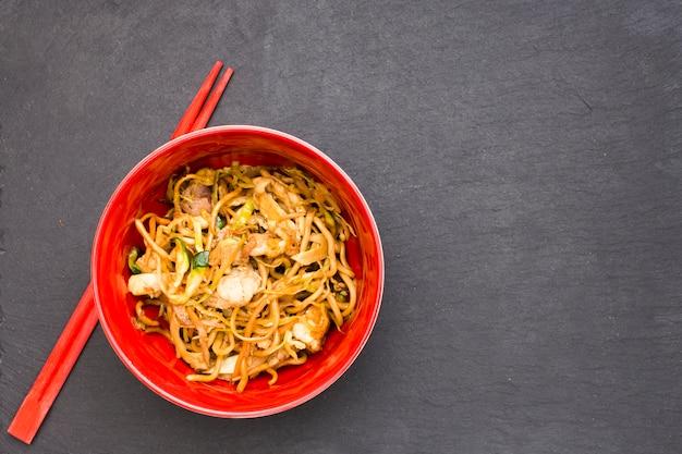 Vue grand angle de délicieuses nouilles chinoises dans un bol avec des baguettes sur une surface noire
