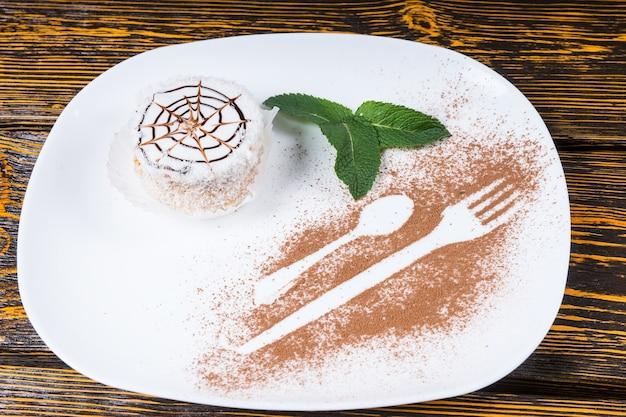 Vue en grand angle d'un dessert décadent avec une conception de toile d'araignée sur une assiette blanche avec une garniture de feuilles de menthe et des contours d'ustensiles saupoudrés de copeaux de chocolat