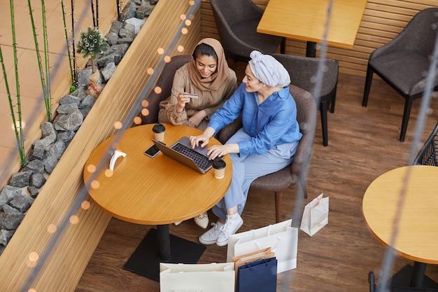 Vue grand angle à deux jeunes femmes du moyen-orient profitant des achats en ligne via un ordinateur portable alors qu'il était assis dans un café du centre commercial et tenant une carte de crédit
