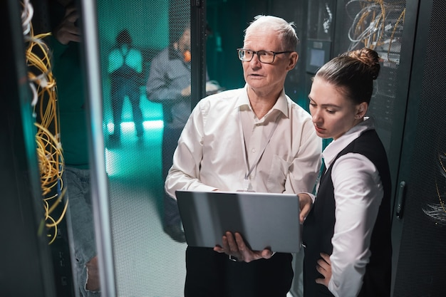 Vue en grand angle sur deux scientifiques des données utilisant un ordinateur portable tout en travaillant avec un superordinateur dans un centre de données, espace de copie