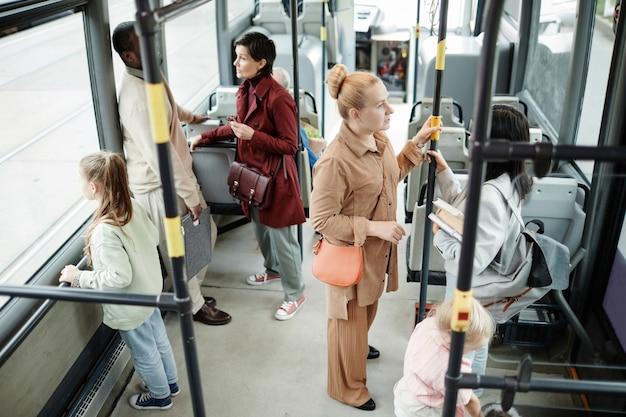 Vue grand angle sur divers groupes de personnes dans un bus public, espace de copie