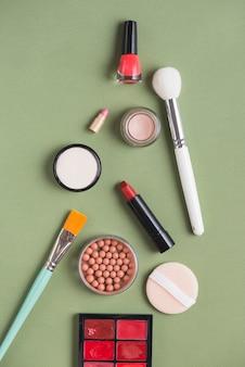 Vue grand angle de divers produits de maquillage sur fond vert