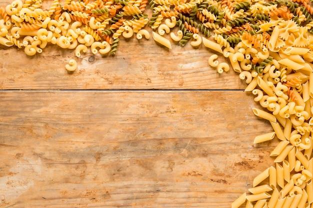 Vue grand angle de divers types de pâtes non cuites sur un bureau en bois