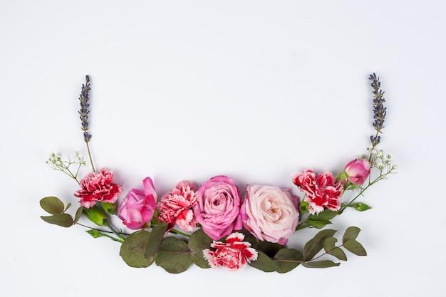 Vue grand angle de diverses fleurs fraîches sur une surface blanche