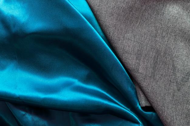 Vue grand angle d'un drap de coton noir et d'un drapé bleu satiné