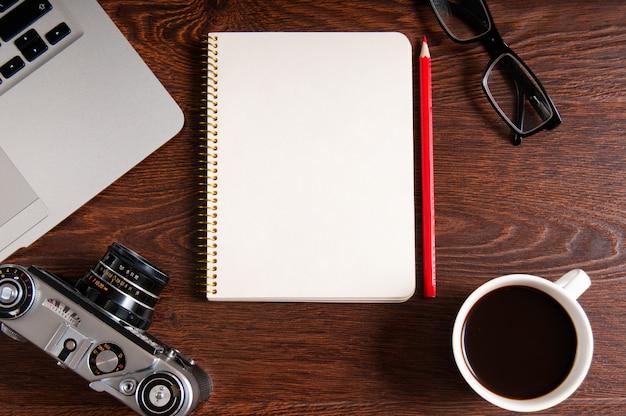 Vue grand angle du bloc-notes avec espace de copie. table avec ordinateur portable et fournitures. vue de dessus. mise à plat. bureau indépendant ou étudiant