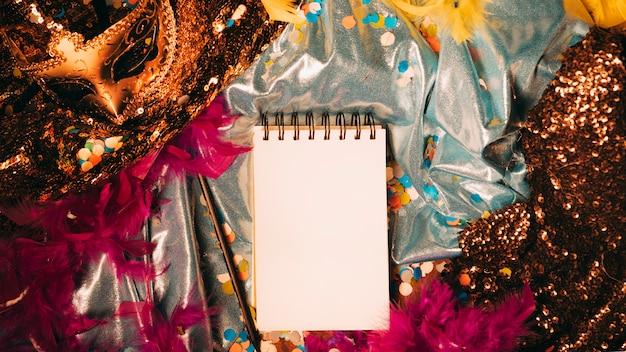 Vue grand angle du bloc-notes vierge en spirale avec des accessoires de carnaval