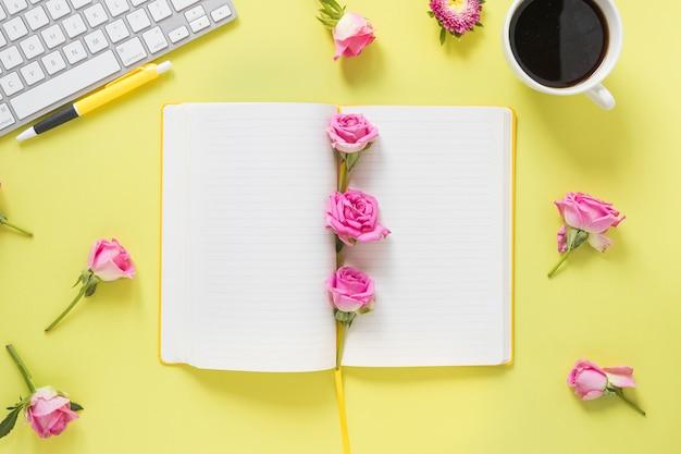 Vue grand angle du cahier; stylo; fleurs; clavier et thé noir sur fond jaune