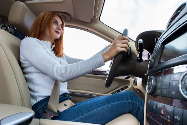 Vue grand angle du conducteur jeune femme rousse attaché par la ceinture de sécurité au volant d'une voiture souriant joyeusement.