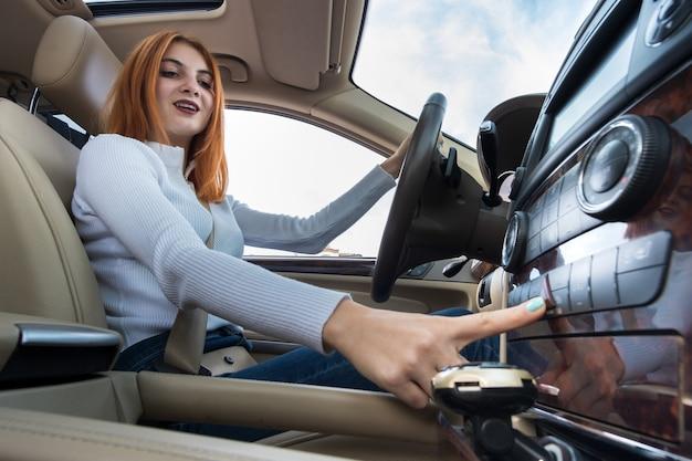 Vue grand angle du conducteur de la jeune femme rousse attachée par la ceinture de sécurité au volant d'une voiture souriant joyeusement.