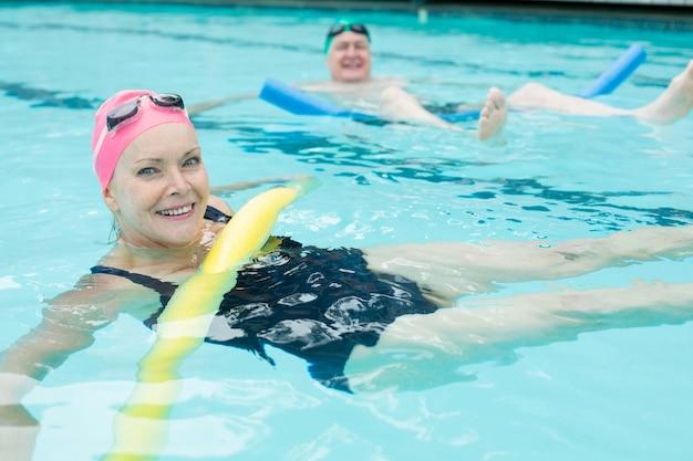 Vue grand angle du couple d'âge mûr nageant avec des nouilles de piscine