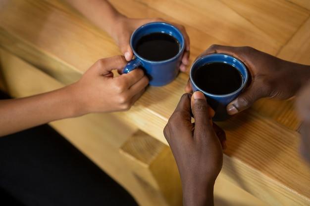 Vue grand angle du couple mains tenant des tasses de café à table au café