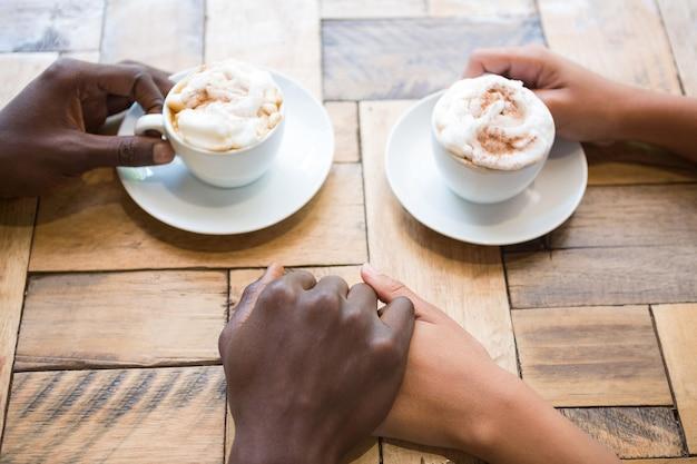 Vue grand angle du couple prenant un café tout en se tenant la main au café