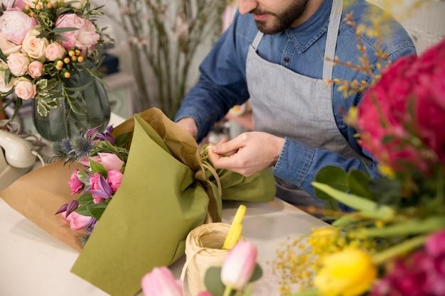 Vue grand angle du fleuriste mâle attachant le bouquet de fleurs