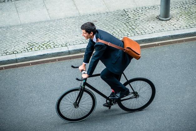 Vue grand angle du jeune homme portant un costume tout en conduisant un vélo utilitaire dans la rue