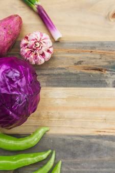 Vue grand angle du piment vert; chou rouge; ail et patate douce sur une planche en bois