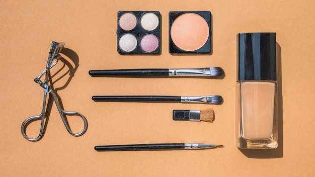 Vue grand angle du recourbe-cils; poudres d'ombre à paupières et brosses sur fond orange