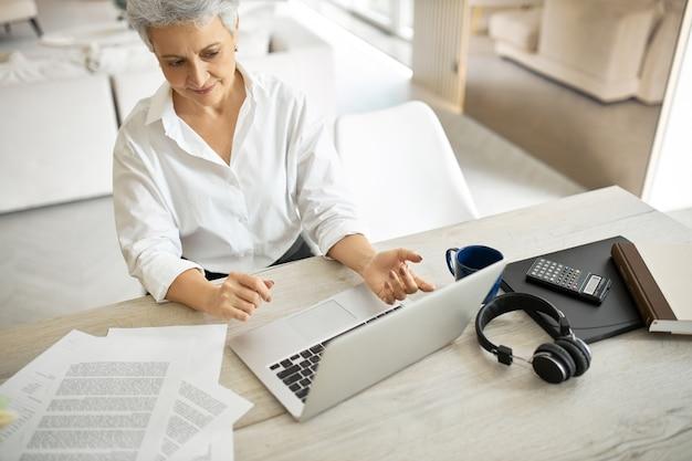 Vue grand angle de l'élégant comptable femme mature confiante à l'aide d'un ordinateur portable générique pour le travail en ligne, la tenue de registres financiers pour les grandes entreprises, assis au bureau avec des papiers