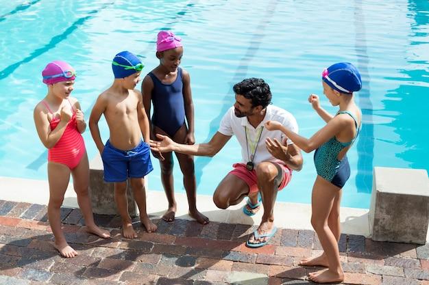 Vue grand angle de l'entraîneur masculin aidant les enfants au bord de la piscine