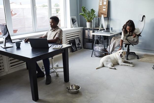 Vue grand angle sur une femme afro-américaine qui caresse un chien tout en travaillant dans un espace de copie de bureau adapté aux animaux de compagnie