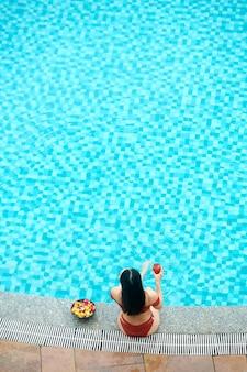 Vue grand angle d'une femme aux cheveux noirs en maillot de bain buvant un cocktail et mangeant des fruits tout en se relaxant ...