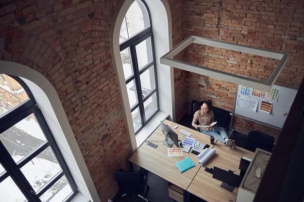 Vue grand angle d'une femme créative regardant la fenêtre tout en étant assise à la table et en travaillant