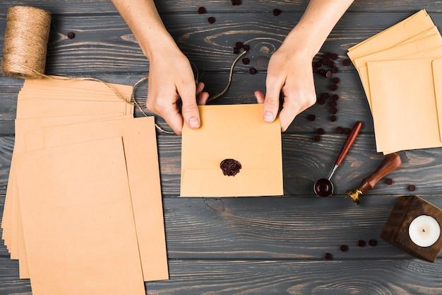 Vue grand angle de femme montrant le phoque sur une enveloppe brune avec du matériel d'artisanat sur une table en bois