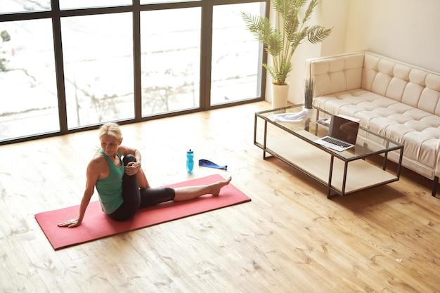 Vue grand angle d'une femme mûre faisant du sport à la maison assise sur un tapis de yoga et l'étirant