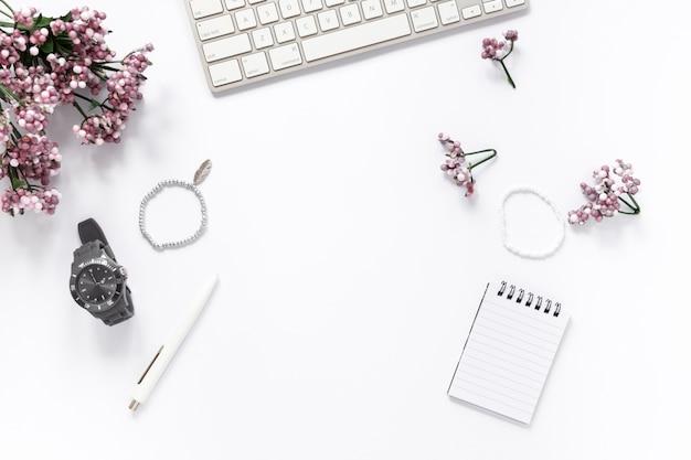 Vue grand angle de la fleur; bracelet; montre-bracelet; stylo; bloc-notes en spirale; et clavier sur fond blanc