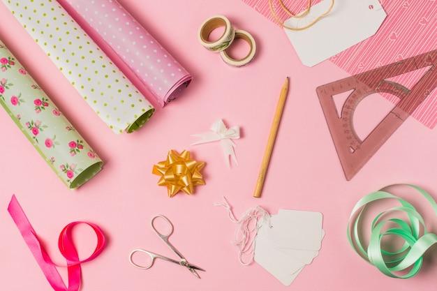 Vue grand angle de fournitures de papeterie avec emballage cadeau et étiquettes sur fond rose