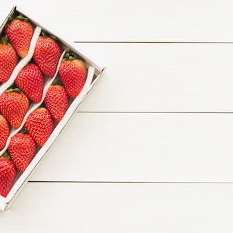 Vue grand angle de fraises fraîches sur fond en bois