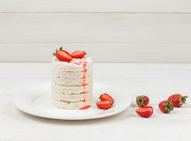 Vue grand angle des gâteaux de riz blanc sur plaque avec des fraises sur la surface de la planche de bois blanc.