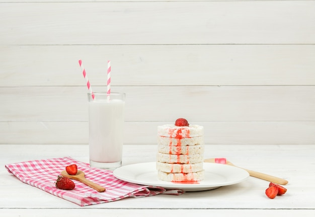 Vue grand angle des gaufrettes de riz blanc sur plaque avec des fraises, des cuillères en bois et du lait sur la surface de la planche de bois blanc.