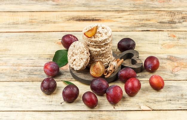 Vue grand angle des gaufrettes de riz sur une planche à découper ronde avec des prunes sur une table en bois. horizontal