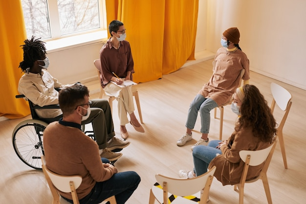 Vue en grand angle sur un groupe diversifié de personnes assises en cercle pendant une séance de thérapie dans une pièce ensoleillée, espace pour copie