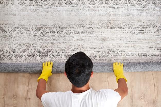 Vue grand angle de l'homme déroulant le tapis. concept de service de nettoyage