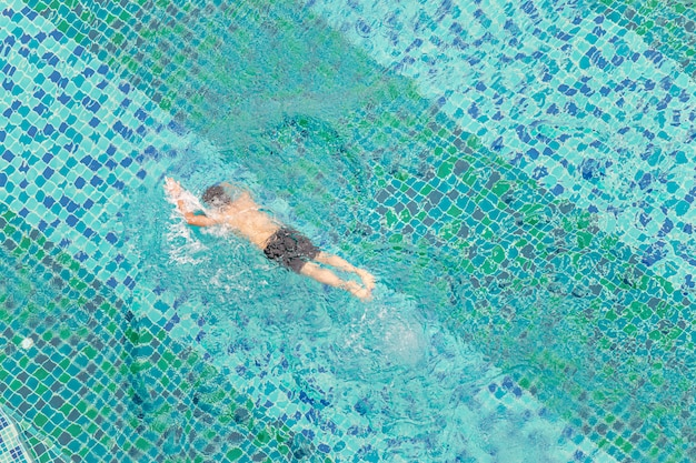 Vue grand angle d'un homme nageant dans une piscine