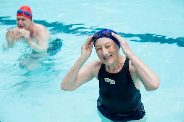 Vue grand angle de l'homme senior et femme nager dans la piscine